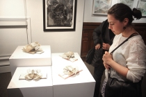 Artist Kremena Stephanova looking at artist Wayne Kleppe's work.