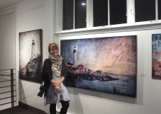 "Mae Chevrette in front of her artwork – ""Ghosts of the Coasts"" and ""Rose Morning"""